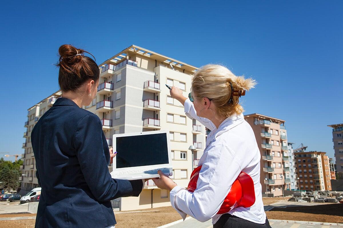 registre des copropriétés deux femmes ordinateur immeuble